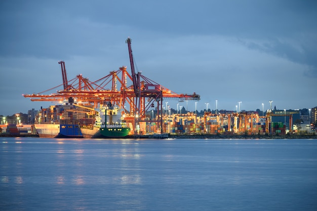 Międzynarodowy statek towarowy z oświetleniem kontenerów i suwnicami w porcie