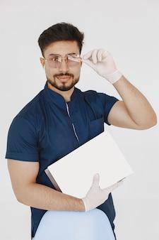 Międzynarodowy student medycyny. mężczyzna w niebieskim mundurze. lekarz ze strzykawką.
