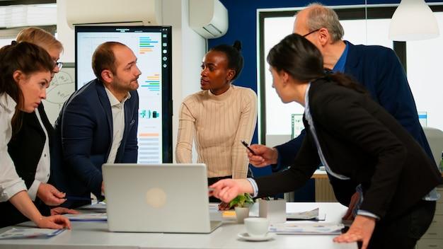 Międzynarodowy zespół biznesowy rozmawiający z afrykańską mentorką omawiającą plan rozwoju firmy stojący przy broadroomie. czarny lider wyjaśniający strategię projektu zróżnicowanej wielorasowej grupie korporacyjnej