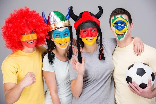 Międzynarodowy zespół z flagami narodowymi namalowanymi na twarzach.