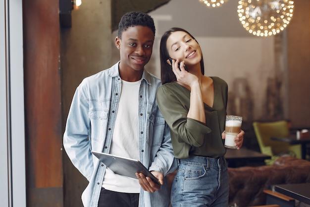 Międzynarodowych ludzi stojących w kawiarni z tabletem i kawą