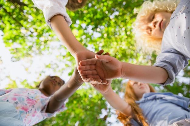 Międzyrasowa grupa dzieci, dziewcząt i chłopców bawiących się razem w parku w letni dzień