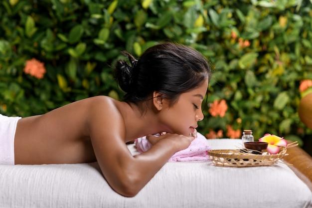 Międzyrasowa młoda dziewczyna pozuje podczas gdy kłamający na masażu stole