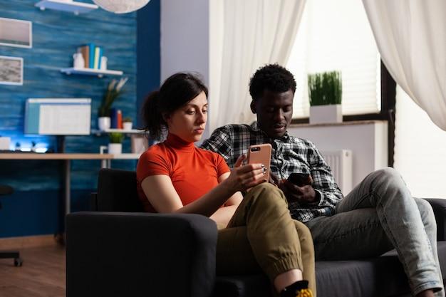 Międzyrasowa para siedzi na kanapie relaks z gadżetami. kaukaski kobieta i afroamerykanin za pomocą smartfonów z technologią. partnerzy rasy mieszanej posiadający urządzenia telefoniczne.