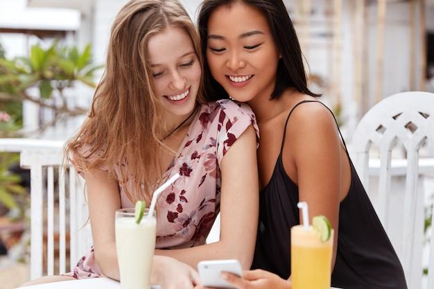 Międzyrasowa para siedzi razem w przytulnej restauracji, ogląda wideo na smartfonie, pije smaczny koktajl, zachwyca wyglądem.