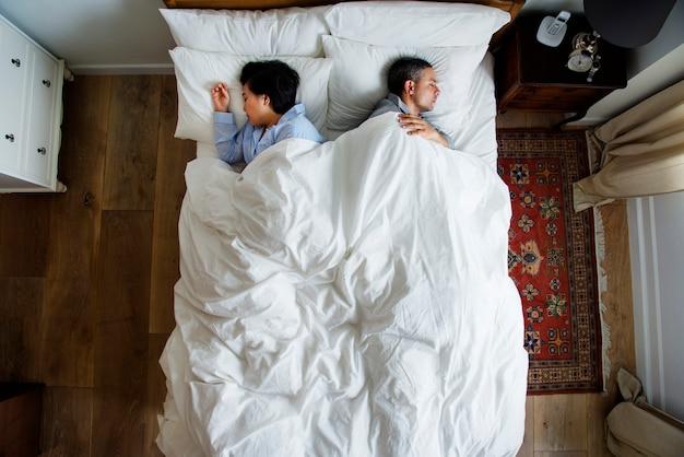 Międzyrasowa para śpi z powrotem do tyłu na łóżku
