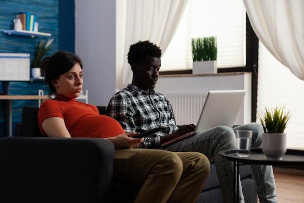 Międzyrasowa para spodziewająca się dziecka i korzystająca z technologii