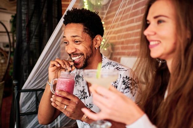 Międzyrasowa para zakochanych pije koktajl w ekskluzywnym barze