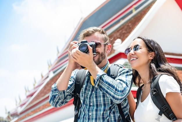 Międzyrasowa turystyczna para bierze fotografie podczas wakacje letni wycieczki w bangkok tajlandia