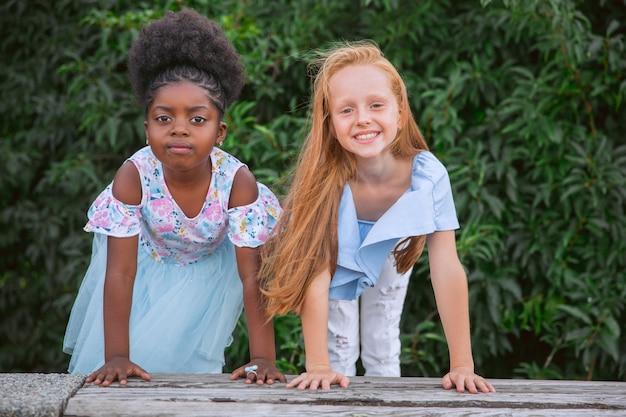 Międzyrasowe koleżanki dla dzieci, dziewczyny bawiące się razem w parku