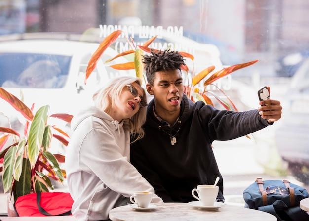 Międzyrasowe para siedzi w kawiarni na świeżym powietrzu przy selfie na telefon komórkowy