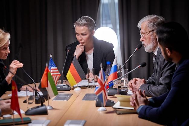 Międzyrasowe podmioty gospodarcze zebrane na spotkanie negocjacyjne prowadzone przez kaukaską bizneswoman, poważna rozmowa wyraźna opinia oferta rozwiązania rozwiąż bieżące problemy, koncepcja partnerstwa