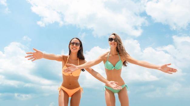 Międzyrasowi kobieta przyjaciele w kolorowych bikini przy lato plażą
