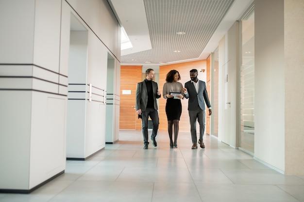 Międzyrasowi koledzy biznesowi spacerujący po korytarzu i omawiający projekt w ruchu