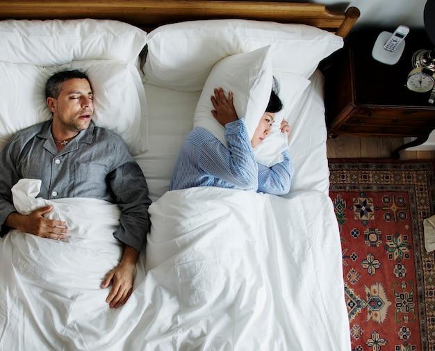 Międzyrasowy para na łóżku mężczyzna chrapa i zakłóca kobiety