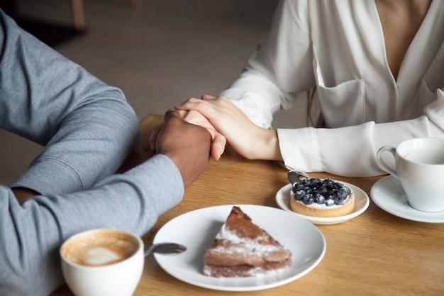 Międzyrasowy pary mienie wręcza obsiadanie przy kawiarnia stołem, zbliżenie widok