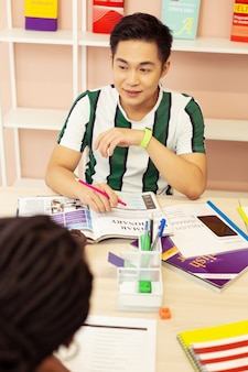 Miej pomysł. miły młody człowiek siedzi w klasie i ćwiczy swój język