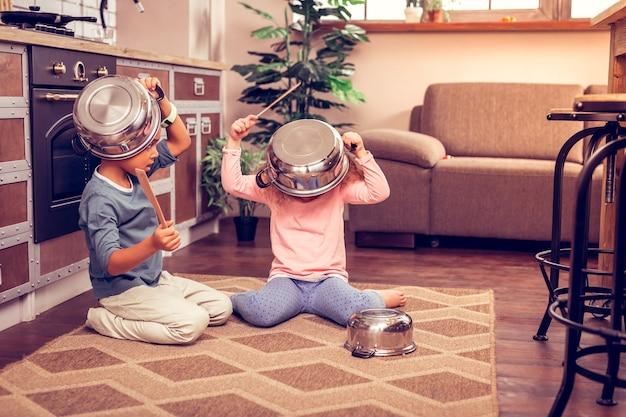 Miej pomysł. uważny chłopak patrzący na swojego przyjaciela i trzymający patelnię na głowie