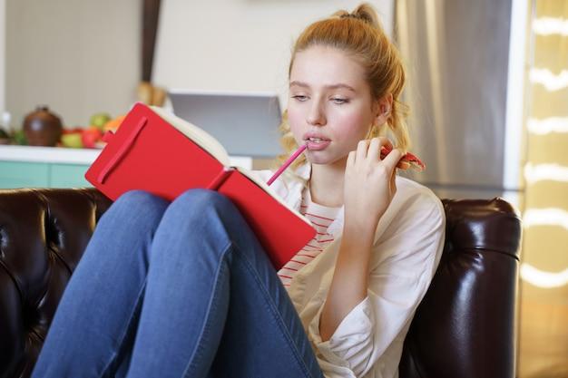 Miej pomysł. zadowolona dziewczyna trzyma kanapkę w dłoni i robi listę planów na dzień
