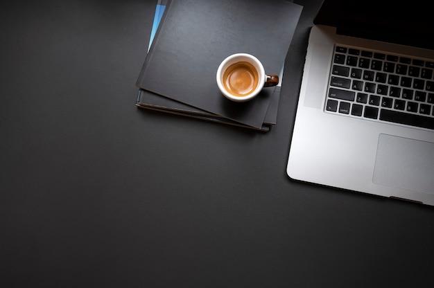 Miejsca pracy pojęcie z laptopem i filiżanką kawy na książkach, odgórny widok.