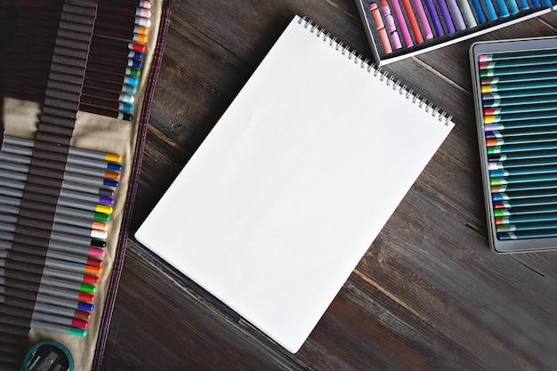 Miejsce do malowania artystycznego, ołówki, pędzle, farby akwarelowe, papier na płótnie i kredki pastelowe. płaski drewniany stół