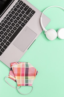Miejsce do pracy lub nauki z szarym laptopem i sprzętem ochrony osobistej.