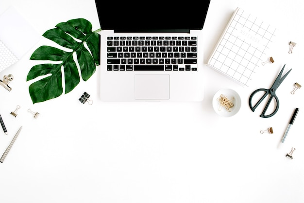 Miejsce do pracy w biurze domowym z laptopem, liściem palmowym, notebookiem i akcesoriami