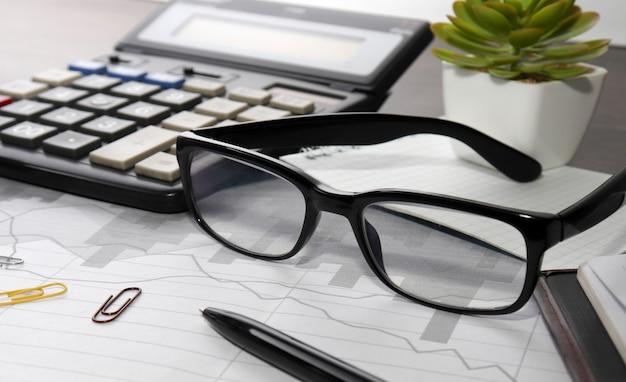 Miejsce do pracy z kalkulatorem, długopisem, okularami i notatnikiem. dane finansowe, analiza pisma odręcznego, biuro na stole. finanse biznesu, technologia edukacji. praca w domu.
