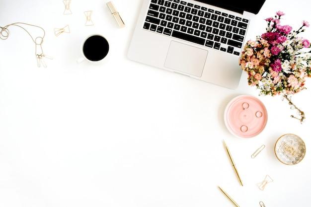 Miejsce do pracy z laptopem, bukietem polnych kwiatów, filiżanką kawy, złotym długopisem, klipsami i akcesoriami