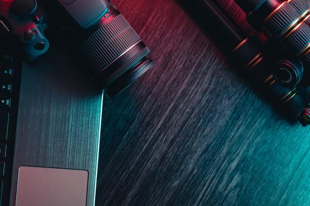 Miejsce do pracy z laptopem, nowoczesnym aparatem, obiektywem i statywem na drewnianym stole.