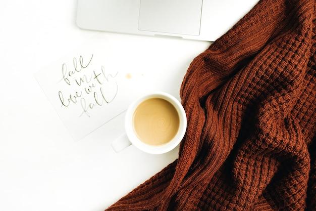 """Miejsce do pracy z ręcznie napisanym cytatem """"zakochaj się w jesieni"""", laptop, kawa, ciepły sweter na białej powierzchni"""