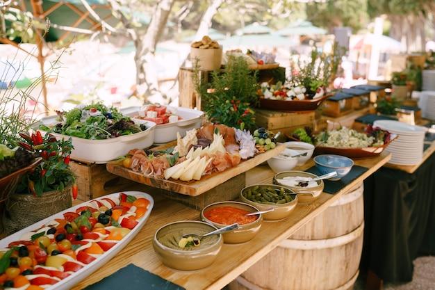 Miejsce do przygotowania potraw na bankiet na łonie natury z talerzami i deskami przysmaków i sałatek