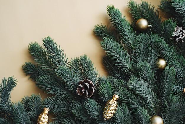 Miejsce na tekst między gałęziami choinki ze złotymi dekoracjami i kulkami na beżowym tle.