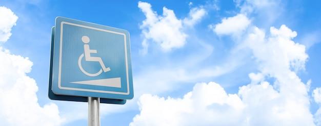 Miejsce parkingowe dla niepełnosprawnych i znak drogowy dla wózków inwalidzkich i symbole na słupie ostrzegającym kierowców na tle błękitnego nieba.