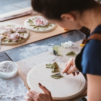 Miejsce pracy artysty. inspiracja. ceramiczna grafika kwiatowa w toku. kobieta z narzędziami do modelowania pracującymi w studio.
