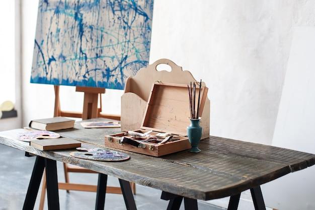 Miejsce pracy artysty. narzędzia graficzne na drewnianym stole. koncepcja edukacji. bałagan w warsztacie artysty, akwarele, pędzle, paleta, sztalugi i narzędzia do malowania. miejsce pracy projektanta, styl hipster.