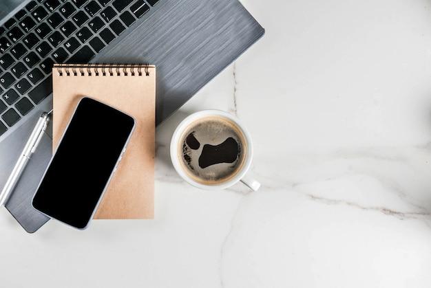 Miejsce pracy, biały stół biurkowy z laptopem, smartfonem, filiżanką kawy i notatnikiem
