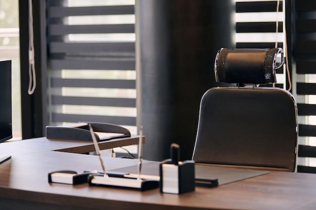 Miejsce pracy biura biznesowego. miejsce pracy dla szefa, szefa lub innych pracowników. stół i wygodne krzesło. światło przez pół otwarte żaluzje