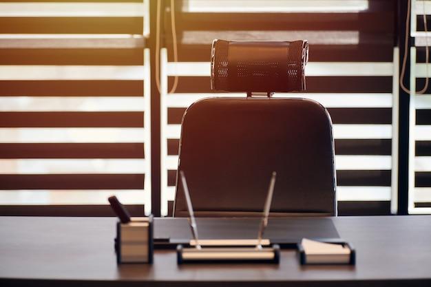 Miejsce pracy biura biznesowego. światło słoneczne w miejscu pracy dla szefa, szefa lub innych pracowników. stół i wygodne krzesło. światło przez pół otwarte żaluzje