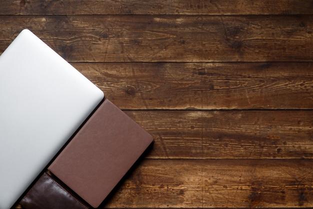 Miejsce pracy biznesmena. widok z góry . notebook do kawy i laptop na pulpicie z czarną notatką.