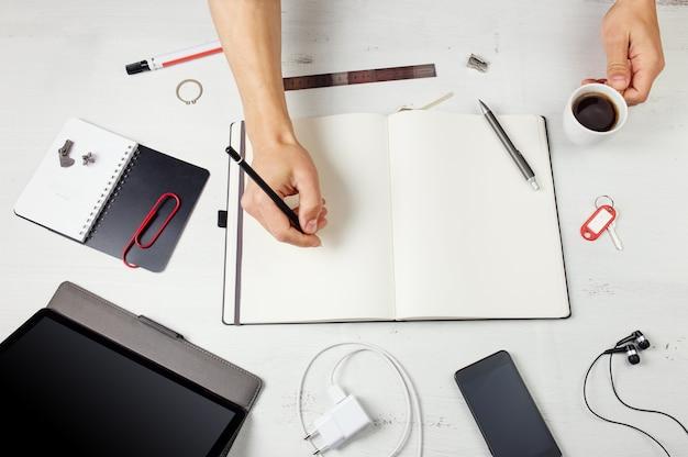 Miejsce pracy człowiek pracujący na notatnik tablet pc i inteligentny telefon na białym drewnianym stole
