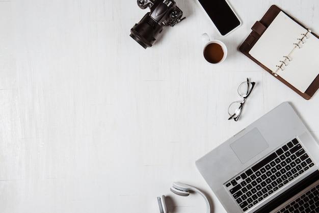 Miejsce pracy dla fotografa, grafika. płaskie ułożenie laptopa, aparatu, kolorystyki, cyfrowego tabletu, filiżanki kawy, książki, ołówka na drewnianym stole.