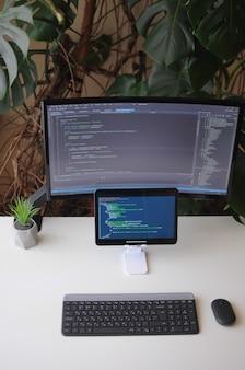 Miejsce pracy dla programisty, ekranu i tabletu z kodem. komfort pracy w domu z roślinami