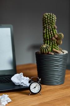 Miejsce pracy, drewniane biurko z zegarem, kartka papieru, laptop, notatnik, zmięte papierowe kulki i materiały eksploatacyjne,