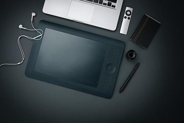 Miejsce pracy firmy. nowożytni męscy akcesoria i laptop na czarnym tle