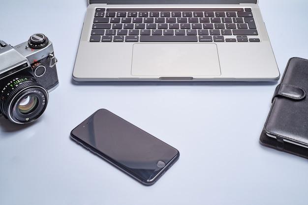 Miejsce pracy fotografa. nowoczesny laptop, aparat cyfrowy, obiektyw, bateria, smartfon. minimalizm. widok z góry. skopiuj miejsce. sprzęt dla fotografa. pojęcie freelancingu