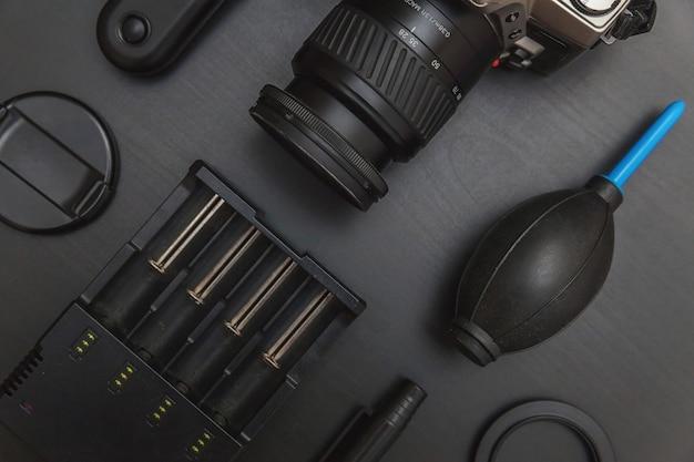 Miejsce pracy fotografa z systemem aparatu dslr, zestawem do czyszczenia aparatu, obiektywem i akcesoriami do aparatu na ciemnym czarnym tle stołu