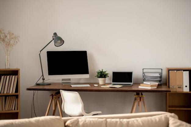 Miejsce pracy freelancera lub pracownika domowego biura ze stołem przy ścianie oraz szeregiem artykułów i gadżetów do pracy