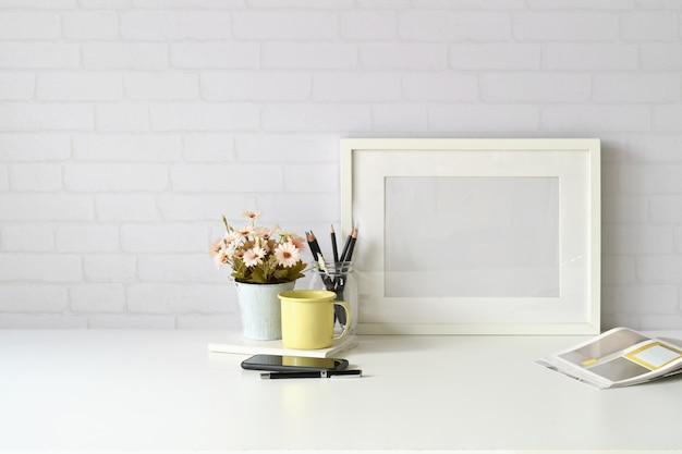 Miejsce pracy i kopia, stylowy obszar roboczy z plakatem makieta, kubkiem kawy i rośliną kwiatową.