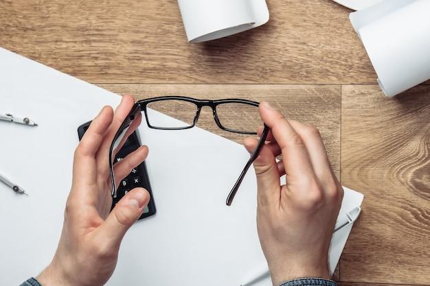 Miejsce pracy inżyniera. męskie dłonie trzymają okulary na stanowisku pracy.